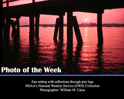 Sun setting with reflections through pier legs. NOAA's National Weather Service (NWS) Collection Photographer: William M. Caine